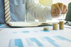 Close-up of Businessman putting coin to rising stack of coins. Close up of Businessman putting coin to rising stack of coins royalty free stock photos