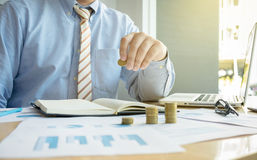 Close-up of Businessman putting coin to rising stack of coins. Close-up of Businessman putting coin to rising stack of coins royalty free stock images
