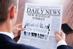 Close-up of businessman reading news on newspaper Stock Photos