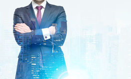 Close up of a businessman in red tie with crossed arms standing against a city panorama. Royalty Free Stock Photo