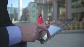 Close up of businessman`s hand browsing tablet, steadicam. Close up of businessman`s hand browsing tablet. He is young and has beard. Man is dressed in suit and stock video footage