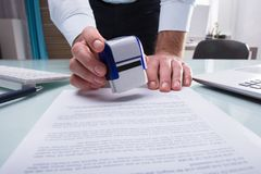 Businessman Stamping Approved On Document. Close-up Of A Businessman`s Hand Stamping Approved On Document In Office stock images