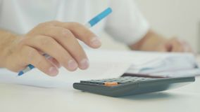 Businessman hand working with finances documents and using calculator in office. Close-up of businessman`s hand working with finances documents and using stock footage