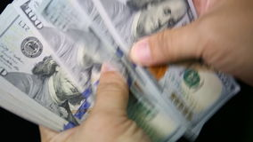 Close-up of a businessman's hands counting dollar bills stock video footage