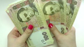 Close-up of a businessman's hands counting hundred  hryvnia bills at a table stock video