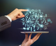 Close-up of businessman's hands and a finger which is pointing out the specific icon on the tablet's projection. Stock Photo