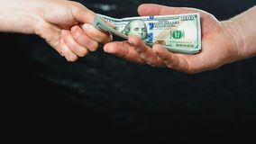 Close up of a businessman`s hands holding money over a black background royalty free stock images