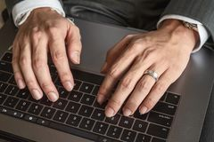Close up of businessman`s hands typing on computer keyboard. Close up of businessman`s hands typing on computer keyboard, wearing silver watch and wedding ring royalty free stock photos