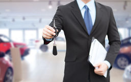 Close up of businessman or salesman giving car key Royalty Free Stock Photo