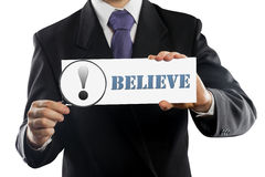 Close up businessman or salesman holding in hands magnifying glass and paper with Believe  message isolated on white Royalty Free Stock Image
