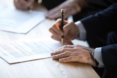 Close up of businessmen sign business contract after briefing. Close up of businessman sign contract legalize paperwork after successful negotiation in office royalty free stock images