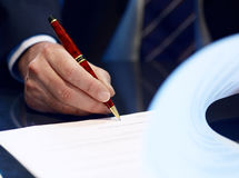 Close up of businessman signing a contract. Businessman sitting at shiny office desk signing a contract with noble classic pen Royalty Free Stock Photo