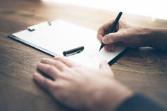 Close-up of businessman signing contract or document on wooden desk royalty free stock image