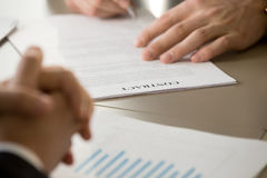 Close up of businessman signing contract at meeting with partner. Businessman signing contract at meeting with partner, male hand putting signature on document Stock Image