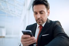 Close up.businessman with a smartphone looking at the camera Royalty Free Stock Images