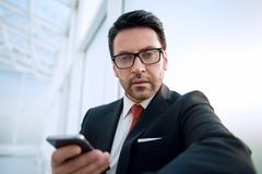Close up.businessman with a smartphone looking at the camera Royalty Free Stock Photos