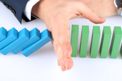 Close-up Of Businessman Stopping The Effect Of Domino With Hand Royalty Free Stock Photo