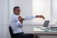 Businessman Relaxing In Office. Close-up Of Businessman Stretching Her Hands At Workplace stock photography