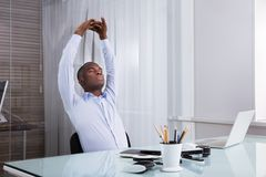 Businessman Relaxing In Office. Close-up Of Businessman Stretching Her Hands At Workplace royalty free stock photography