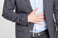 Close-up of businessman with strong stomach pain Royalty Free Stock Photos