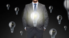 Close up of businessman in suit with ligh bulbs Stock Images