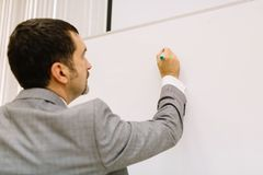 Close-up man writing on a light desk background. Lecturer next to a multimedia projector. Teacher work concept. Close-up of a businessman in a suit working on a royalty free stock photography