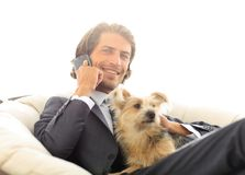 Close-up of a businessman talking on the phone and holding his pet. Stock Image