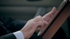 Close up of businessman using digital tablet. Close up of hands using digital tablet while sitting on backseat of a car stock video