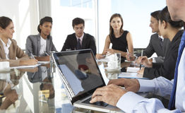 Close Up Of Businessman Using Laptop During Board Meeting Around stock photography