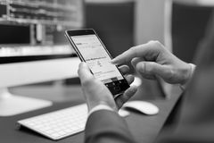 Close up of businessman using mobile smart phone. Close up of a businessman reviewing data on smart phone in corporate office. Focus on mobile device. Black and Stock Image