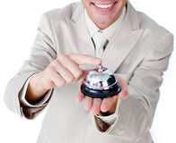 Close-up of a businessman using a service bell. Close-up of a smiling businessman using a service bell isolated on a white background Royalty Free Stock Photography