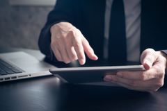 Close up of Businessman using tablet on the office desk. royalty free stock photography
