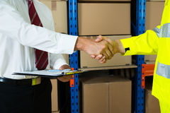 Close-up Of Businessman And Warehouse Worker Shaking Hands. Close-up Of Businessman Holding Clipboard Shaking Hands With Warehouse Worker Royalty Free Stock Photography