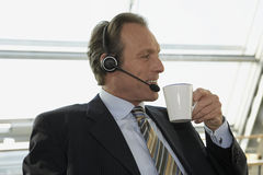 Close-up of a businessman wearing headset and holding a cup of tea. Close-up of a businessman wearing headset and holding a mug of tea stock photos