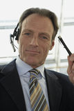 Close-up of a businessman wearing headset and holding a pen.  stock image