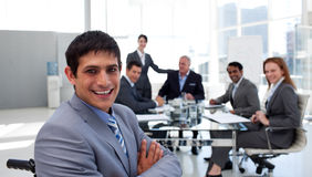 Close-up of a businessman in a wheelchair. With his colleagues in the background stock photo