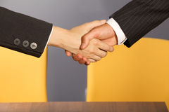 Close-up of businessman and woman shaking hands in office Stock Photography