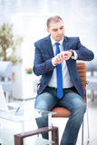 Close up of Businessman working on the desk and checking time. On his wrist watch Royalty Free Stock Photography