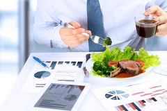 Close-up of businessman working on marketing strategy during business lunch, eating  juicy club steak.  Stock Images