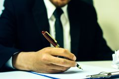 Close-up Of A Businessman writing on a notebook,. Hand Signing Cheque In Office Stock Photography