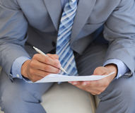 Close-up of a businessman writing on a paper Stock Image