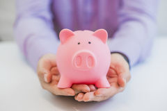 Close-up Of Businessman's Hand Holding Piggybank Over White Background. Stock Photos