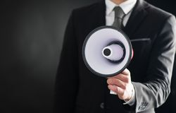 Close up of businessmans hand holding megaphone Royalty Free Stock Image
