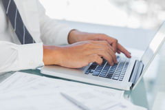 Close up on businessmans hands typing on his laptop Royalty Free Stock Photos