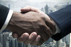 Close up of businessmen shaking hands with cityscape in the background Royalty Free Stock Images