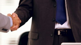 Close up of businessmen shaking hands. In the workplace stock footage