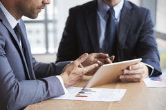 Close Up Of Businessmen Using Digital Tablet In Meeting Royalty Free Stock Photo