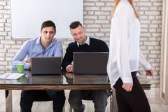 Businessmen Looking At Woman. Close-up Of Businessmen Using Laptop Looking At Woman In Office Stock Images