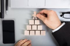Businessperson Arranging Human Figure Cut Out On Wooden Blocks Stock Photo