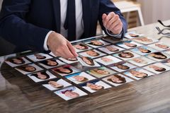 Businessperson Choosing Photograph Of Candidate royalty free stock image